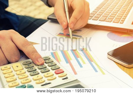 young man accountant working and writing with calculator laptop computer report sheet mobile smartphone finances and counting cost on desk savings business economy concept selective focus
