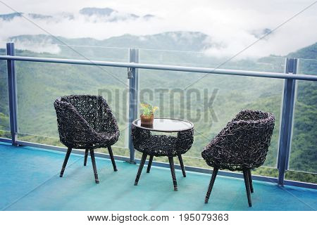Rattan table and chairs set for relaxing and admiring misty valley views with selective focus.