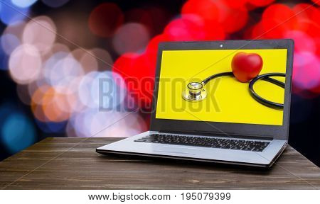 Laptop computer with red heart and stethoscope on yellow background in screen on wood table with blurred night light bokeh background selective focus heart health care and medical technology concept