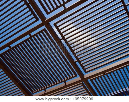 Modern design pergola arbor made wood and metal with clear blue summer sky background