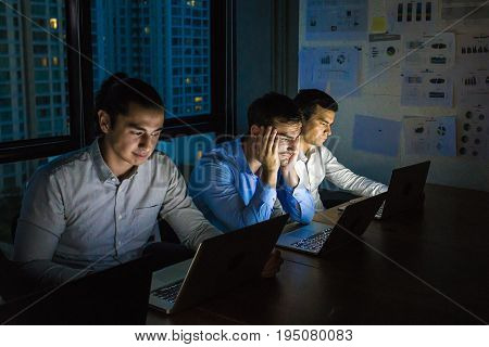 business team working late at night with lights off and computers laptop screen light on. Business people working hard concept. 20-30 year old.