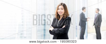 Confident Asian business woman standing and crossing her arms in office building hallway - panoramic banner