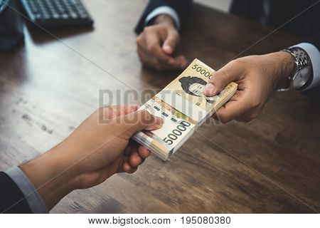Businessman giving money South Korean won banknotes to his partner at the desk