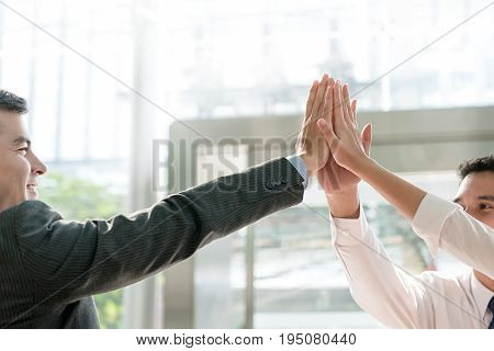 Group of business colleagues giving high five empower each other