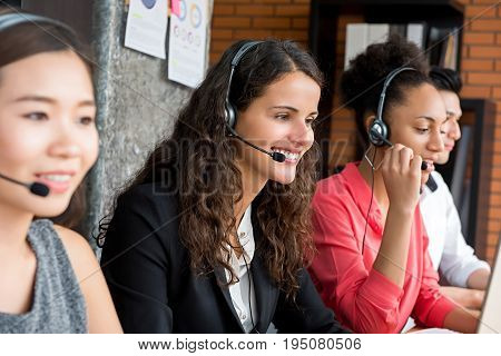 Multiethnic business team working in call center as the operators or telemarketers