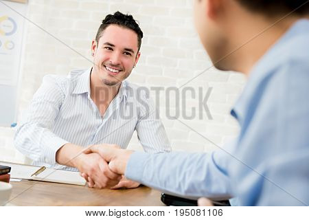 Smiling casual Hispanic businessman making handshake with his partner in the meeting