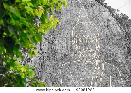 Golden Big Buddha on the mountain Khao Chi Chan Pattaya Thailand whit green leaf foreground