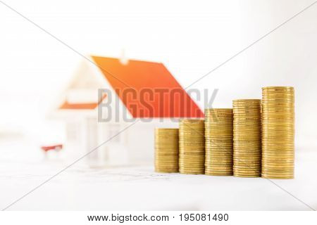Money and house model on blueprint paper - real estate financial and investment concept