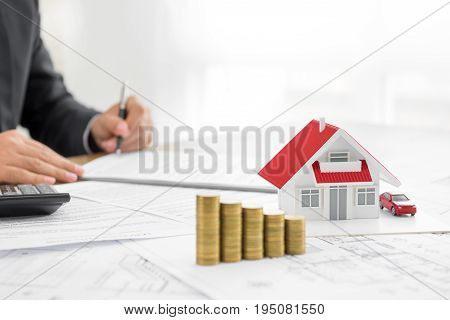 Businessman signing document with money and house model on the table - real estate properties and investment concepts