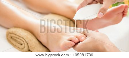 Therapist pouring oil to a woman foot about to give massage in spa - panoramic banner