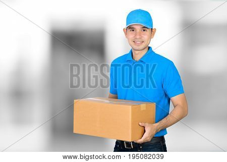 Deliveryman carrying a cardboard parcel box on blur white gray background