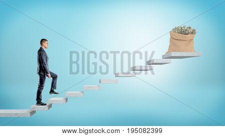 A businessman walking concrete steps made of flying grey slabs to reach a money bag full of dollar bills. Road to success. Personal wealth. Goal of prosperity.