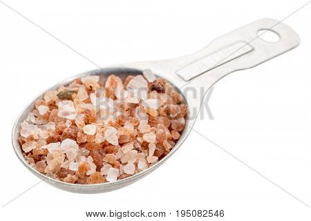 isolated measuring tablespoon of Himalayan salt - pink and orange coarse crystals