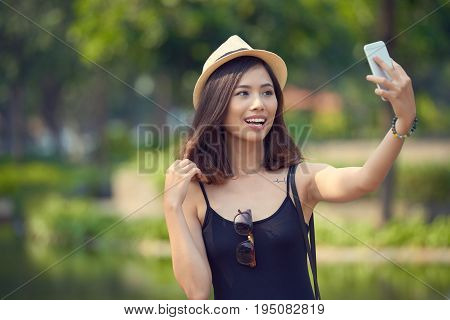 Pretty Vietnamese woman wearing straw hat standing at picturesque lake and taking selfie on smartphone, blurred background
