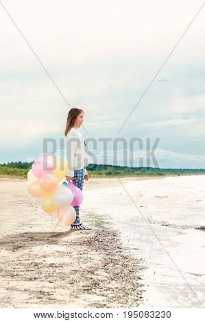 Young teenage girl with multicolored balloons standing on the coastline with blue dramatic cloudy sky background. Multi-colored summertime outdoors vertical image with filter.