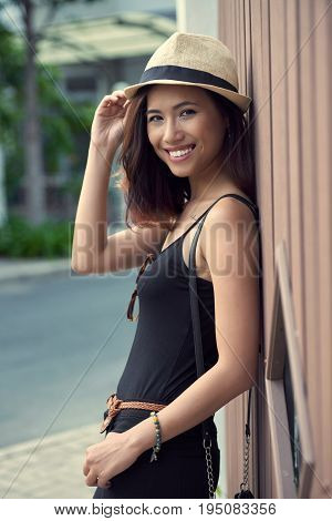 Waist-up portrait of attractive young woman holding brim of straw hat while looking at camera with wide smile, profile view