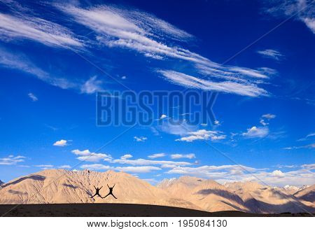 Silhouettes of two people jumping with the backdrop of Himalayan mountains in Nubra Valley, Ladakh, India