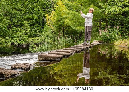 Woman is taking photographs of a stream in Michigan's Upper Peninsula