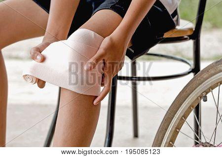 close up little girl touching knee with elastic bandage