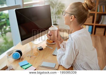Ambitious young financial manager sitting in front of computer with cup of fragrant tea and preparing annual accounts, profile view
