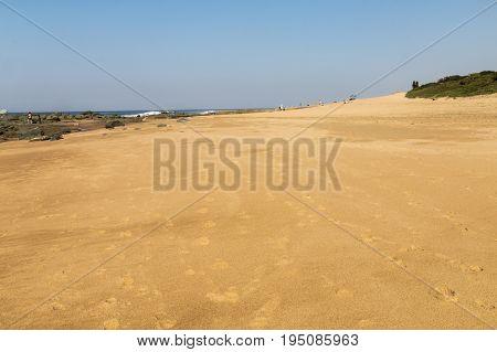 Sandy Beach And Rocky Shoreline Against Blue Sky