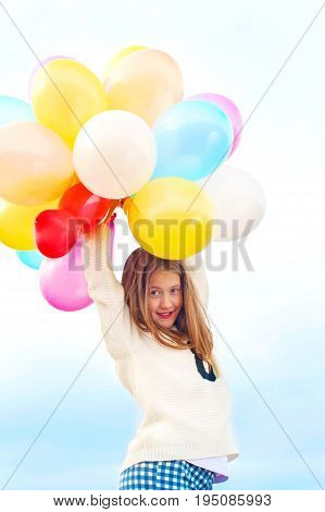 Beautiful smiling young trendy girl with bunch of colored balloons. Outdoors. Filtered image.