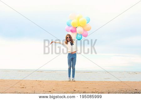 Funny smiling happy girl with many colored air balloons on the seaside. Outdoors. Filtered image.
