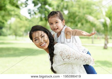 Beautiful Vietnamese woman playing with her daughter in the park
