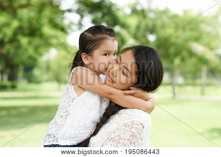 Cute little mixed-race girl kissing her mother on cheek
