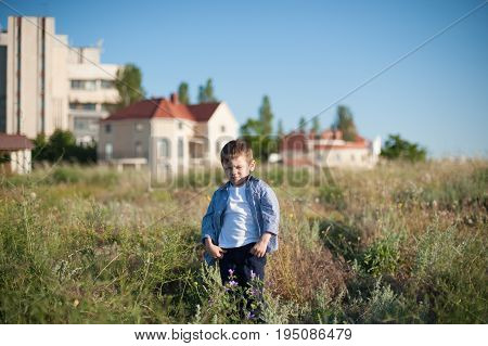 cool little boy with a grimace on his face stands in a field on the background of houses