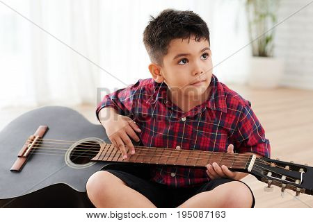 Mixed-race boy sitting on the floor and playing guitar