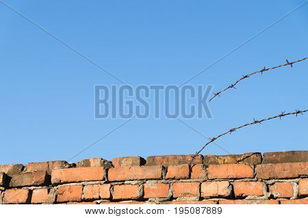 Brick wall, torn barbed wire and blue sky. Red brick fence with security wire under clear blue sky