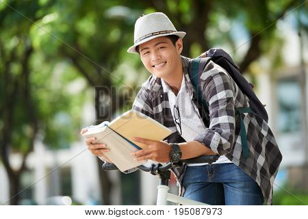 Smiling college student leaning on handlebar and reading a book