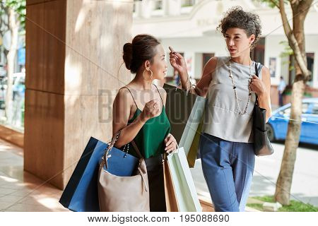 Female shopaholics discussing sale and seasonal offers