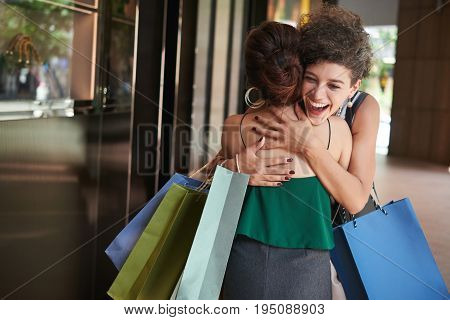Happy woman hugging her friend she met in a mall