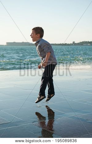 Laughing caucasian jumping little boy in the background of a sea storm