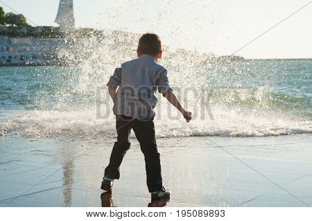 cautious little caucasian boy on the background of a big wave in the city