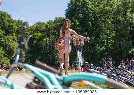 Fashionable woman walking along her stylish vintage bicycle passing trough Englischer Garten in Munich, Germany on hot sunny summer day. People in park enjoying summer and relaxing on greenery.