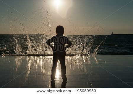 Silhouette of a small boy against the backdrop of a huge wave lit by the sunset in California