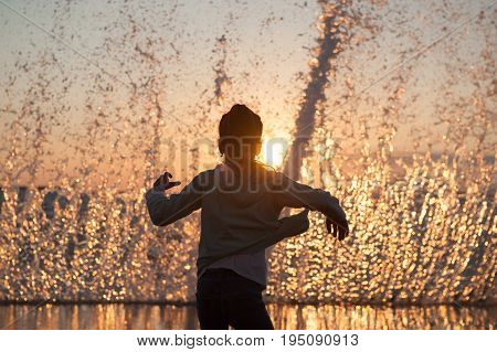 scared school age girl on a background of huge sea wave at beautiful sunset
