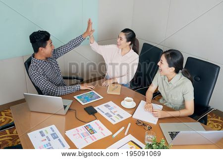 Business people giving high five after first success