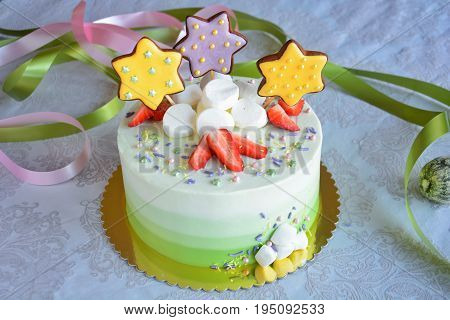 Delicious white and green ombre cake with strawberries marshmallows and gingerbread stars on white background