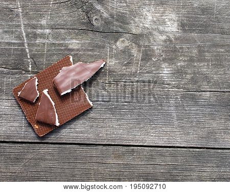Broken chocolate on a wooden background with space for your text.