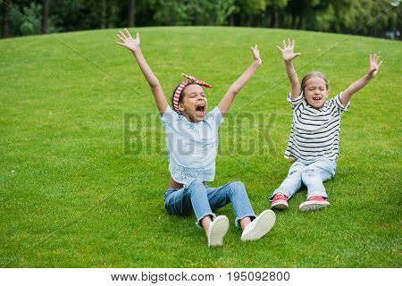 Cheerful multiethnic girls raising hands while sitting on green meadow