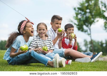 Happy Multiethnic Children Eating Green Apples While Sitting Together On Green Grass
