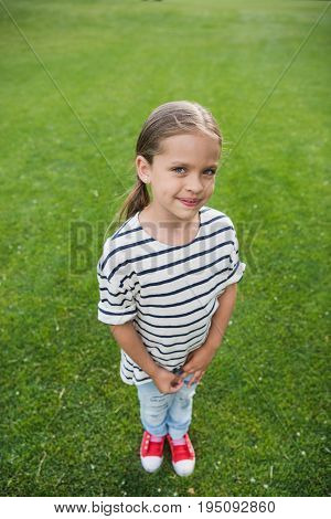 High Angle View Of Adorable Little Girl Standing On Green Grass And Smiling At Camera