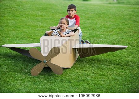 Cheerful Little Friends Playing With Toy Plane On Green Lawn In Park