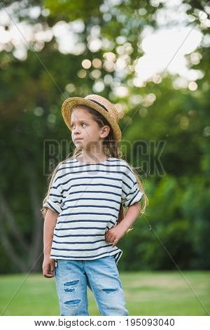 Adorable Little Girl In Straw Hat Standing With Hand On Waist And Looking Away In Park