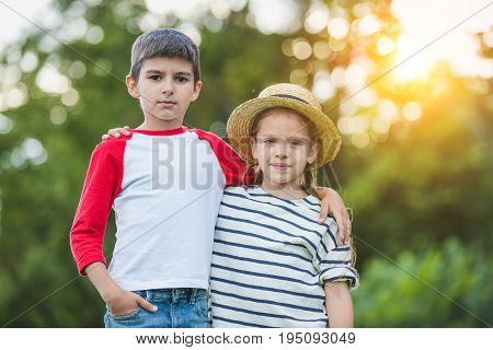Adorable Little Brother And Sister Standing Embracing And Looking At Camera In Park