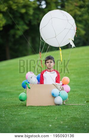Adorable Little Boy Playing With Diy Hot Air Balloon In Park